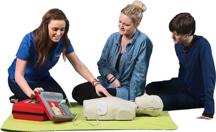 A lady in a skillbase first aid shirt showing two people how to use a defibrillator on a manikin