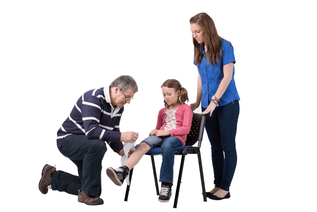 a small girl sits on a chair whilst a man bandages her right Knee. A woman is stood behind the chair overlooking the procedure.