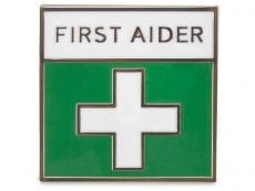 A small square pin badge that has a white cross on a green background and the text : First Aider