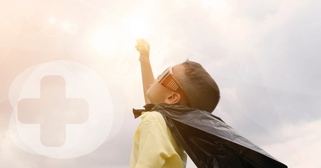 A small child with a cape made from a bin liner looking up at the sun.